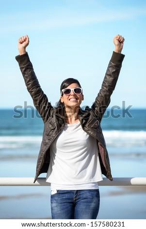 Coast travel joyful woman success. Happy successful hispanic girl enjoying trip to the beach raising arms and smiling on sea background.