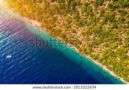 Photo of  Coastal area with blue clear water and forest on land, aerial view taken by drone. Half land half sea on a diagonal line. A picturesque place where transparent turquoise water meets a stony shore.