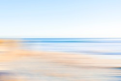 Coastal beachside blur in soft tones of blue and brown.