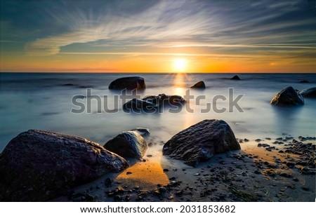 Coastal boulders on the beach at dawn. Sunrise on sea beach. Early morning beach at dawn. Sea beach at dawn