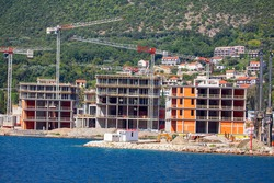 Coastal Construction Site . Construction of new hotels at Kotor Bay . Working industrial cranes