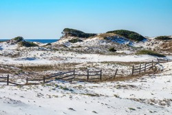 Coastal dunes with rail fence in disrepair on a sunny morning at Deer Lake State Park in the Florida Panhandle