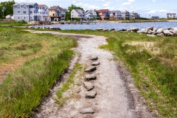 Coastal gravel road with the small seaside neighborhood on the background in East Greenwich, Rhode Island