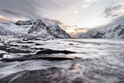 Coastal landscape in winter with water movement over large stones, in the background a mountain range with snow, contrasting colorful sky at sunrise - Location: Norway, Lofoten