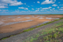 Coastal landscape with sandy seabed at low tide. some green grass from the dike. Low and high tide on the North Sea coast at Dagebüll, Amrum, Sylt, Föhr, destination Germany. blue sky,
