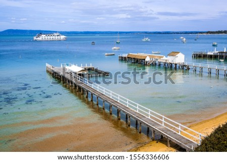 Coastal landscape - wooden piers extending into shallow bay water with passenger ferry sailing in the distance. Melbourne, Victoria, Australia #1556336606