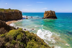 Coastal limestone rocks in the foam of the ocean surf. Travel to the Southern Hemisphere. Pacific coast and sandy beach. Fabulous journey to Australia.