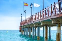 Coastal pier rising into the Mediterranean sea in Marbella Costa del Sol Spain. The pier has concrete columns. There is a Spanish flag and public lighting lamps on the pillar
