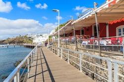 Coastal promenade with restaurant building on side in Puerto del Carmen port, Lanzarote, Canary Islands, Spain