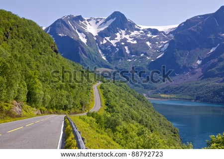 Coastal road in Norway leading to Bodo with snowy mountains of Saltfjellet-Svartisen National Park in the background
