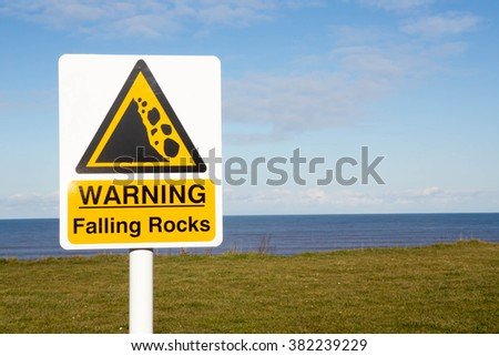 Coastal Sign Warning Of Falling Rocks Due To Erosion Of The High Cliffs