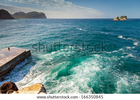 Coastal stones and small pier with breaking waves. Adriatic Sea