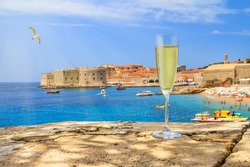 Coastal summer landscape - view of a wineglass of champagne against the background of the Old Town of Dubrovnik on the Adriatic coast of Croatia