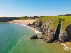 Coastal view of Barafundle Bay Beach, Pembrokeshire, Wales UK. A calm blue and turquoise ocean in a tropic-like setting.
