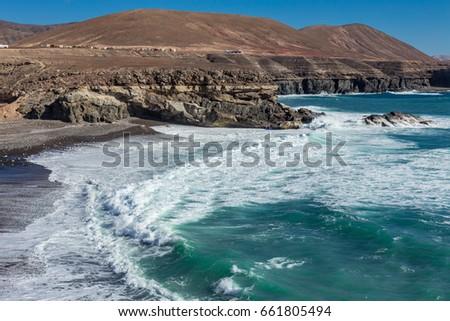 Coastline and cliffs,  stormy white sea waves hitting black beach, frozen motion, geologic layers, Playa Ajuy, Fuerteventura, Canary Islands, Spain  2017 #661805494