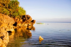 Coastline in Siquijor. Rocks in the water. Sunset in The Philippines. Beautiful light just before sunset. Colorful fishing boats in the background. Beautiful landscape on a Filipino island.