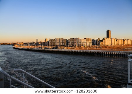 Coastline of Ostend city in the rays of the sunset as seen from the deck of a ferry departs - stock photo
