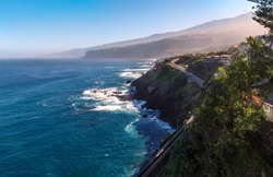 Coastline of the Atlantic ocean with mountains and road view in Puerto de la Cruz, one of the popular resort in the northern part of Tenerife island, Spain.
