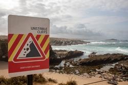 Coastline with warning cliff sign, Porto Covo, Sines, Portugal.