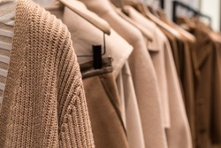 Coat and sweater light brown on the hanger in the store. Classic women's fashion clothes.