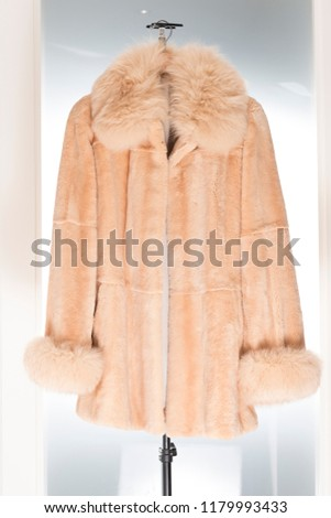 Coat belonging to a collection of fur coats, vison etc Very expensive, brand and haute couture On white background hanging on hangers  #1179993433
