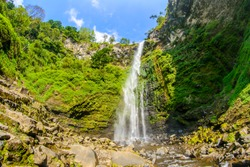 coban rondo waterfall inside a green forest in pujon, malang, east java, indonesia