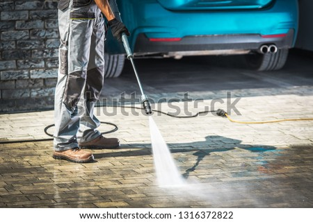 Cobble Driveway Pressure Washing by Caucasian Worker.