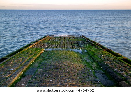 Cobbled boat slipway leading into the sea, lit by the morning sun.