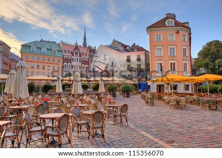 Cobbled city square with outdoor restaurants among colorful buildings in Riga, Latvia.