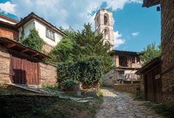 Cobbled lane street with old church in rustic Rhodope mountain village Kovachevitsa,Bulgaria