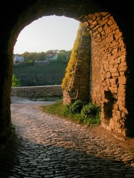 cobbled road leads through the archway made in the stone wall