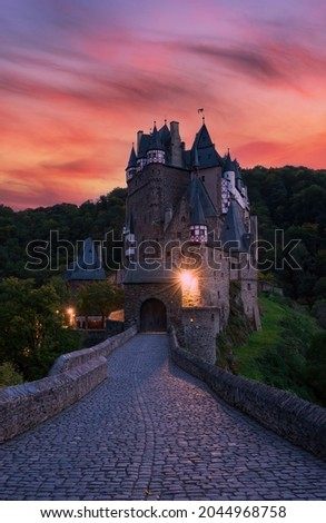 Cobbled road to medieval Burg Eltz castle at twilight, Rhineland-Palatinate, Germany. Burg Eltz is a popular travel destination in Rhineland-Palatinate, Germany. Picturesque burning clouds at sunset Foto stock ©