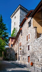 Cobbled street ascending on hillside to Annecy Castle along old stone wall, Annecy, France