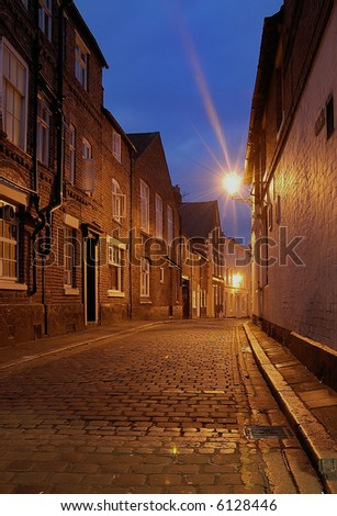 Cobbled street just before dawn showing town houses and street lamps.