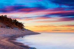 Cobblestone beach with vibrant cloudy ocean sunset background