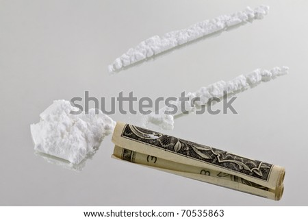 Cocaine cutted at mirror and ready to be sniffed trough a one dollar bill