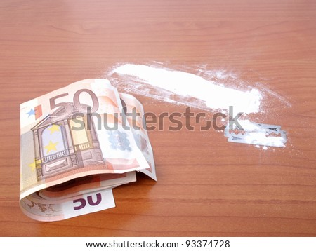 Cocaine drug with money and razor blade - Note: simulated with wheat flour, no real drugs used - stock photo