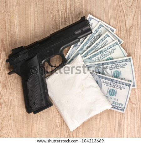 Cocaine in package, dollars and handgun on wooden background