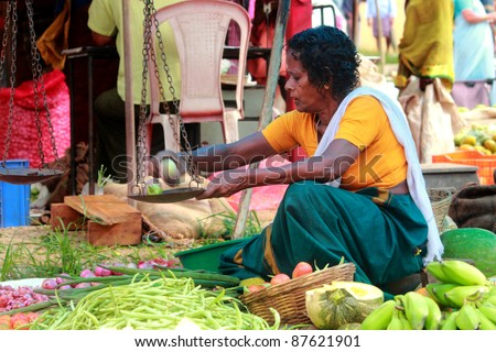 COCHIN - OCTOBER 29: Unidentified old woman sells vegetables in a crowded market October 29, 2011 in Cochin, India. Its a common practice in India to sell vegetables in open markets and streets.