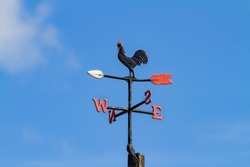 Cockerel Rooster weather vane, wind vane, weathercock against blue sky. Cast iron wind direction instrument, with letters for compass points, painted black red and white. Dublin, Ireland