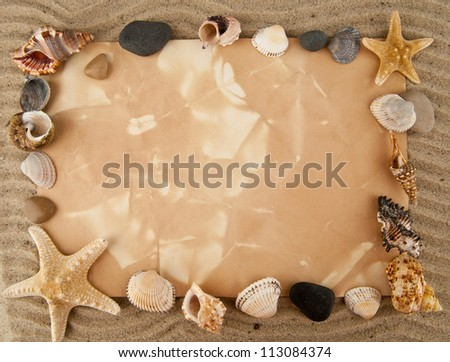 cockleshells, stone, paper on sand