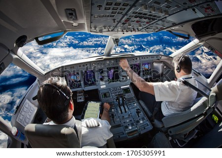Cockpit of the modern passenger aircraft in flight. Pilots fly an airplane over the mountain landscape. Blue cloudy sky is visible outside the cockpit.
