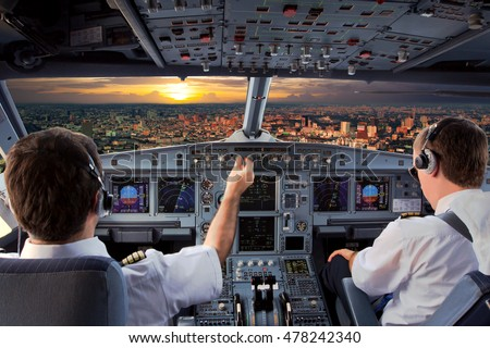 Cockpit view of modern airplane in flight during the sunset. Aircraft pilot at work. #478242340