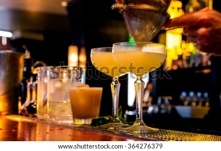 Cocktail being poured at a bar. Motion blur of the bartender\'s hand and strainer. Selective focus on the foreground glass.