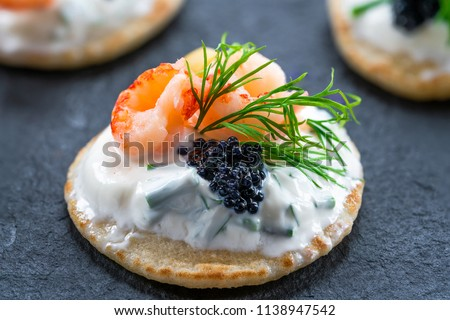 Cocktail blinis with crayfish, caviar and sour cream - gourmet party food. Stock photo ©