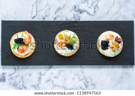 Cocktail blinis with crayfish, caviar and sour cream - gourmet party food - top view Stock photo ©