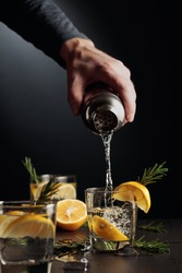 Cocktail Gin and Tonic with lemon and rosemary. The bartender pours a cocktail from a shaker into a glass.