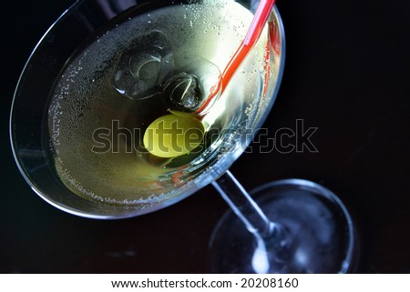 Cocktail glass with ice and olive close-up over black background