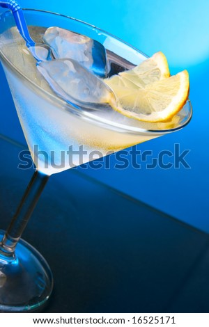 Cocktail glass with ice cubes and lemon slice close-up