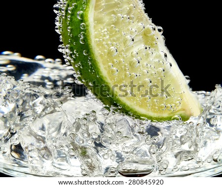 Cocktail glass with lime slices and ice cubes isolated on white background